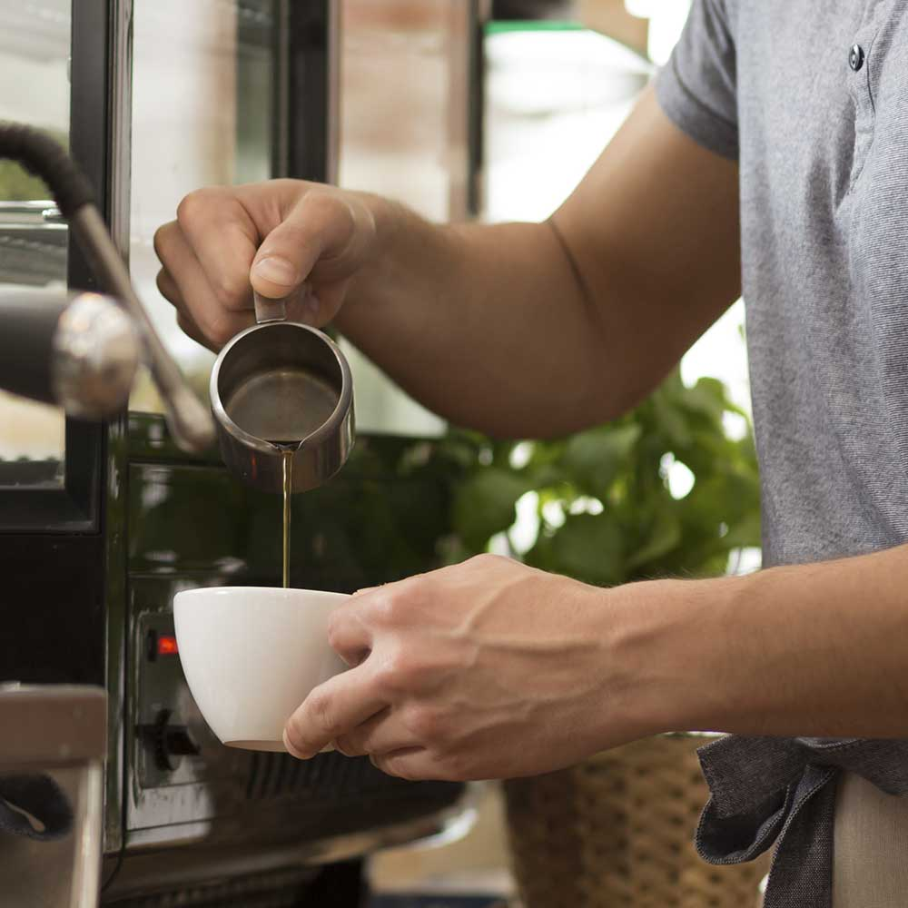 Coffee shop barista pouring coffee