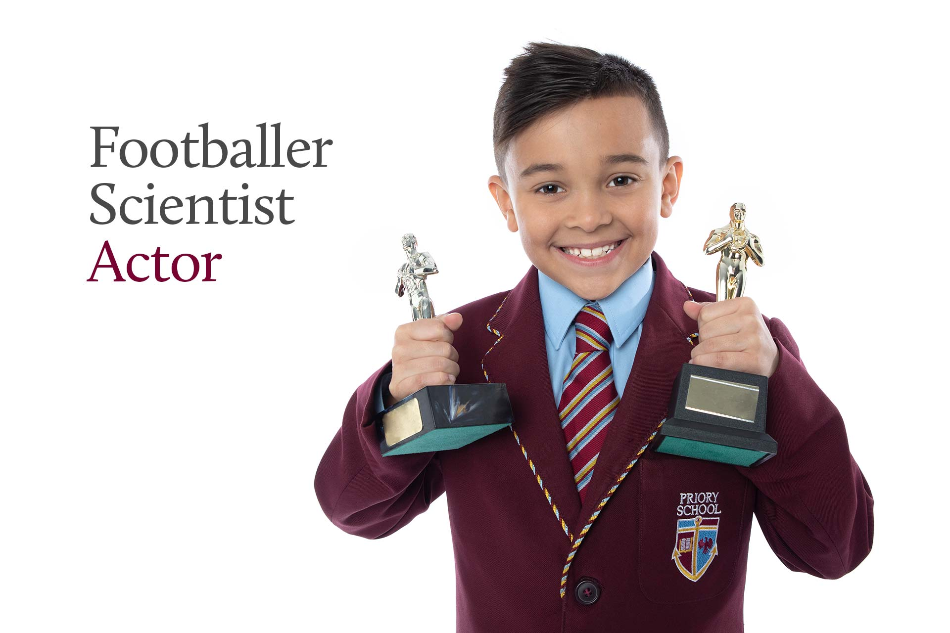Priory School pupil holding academy awards