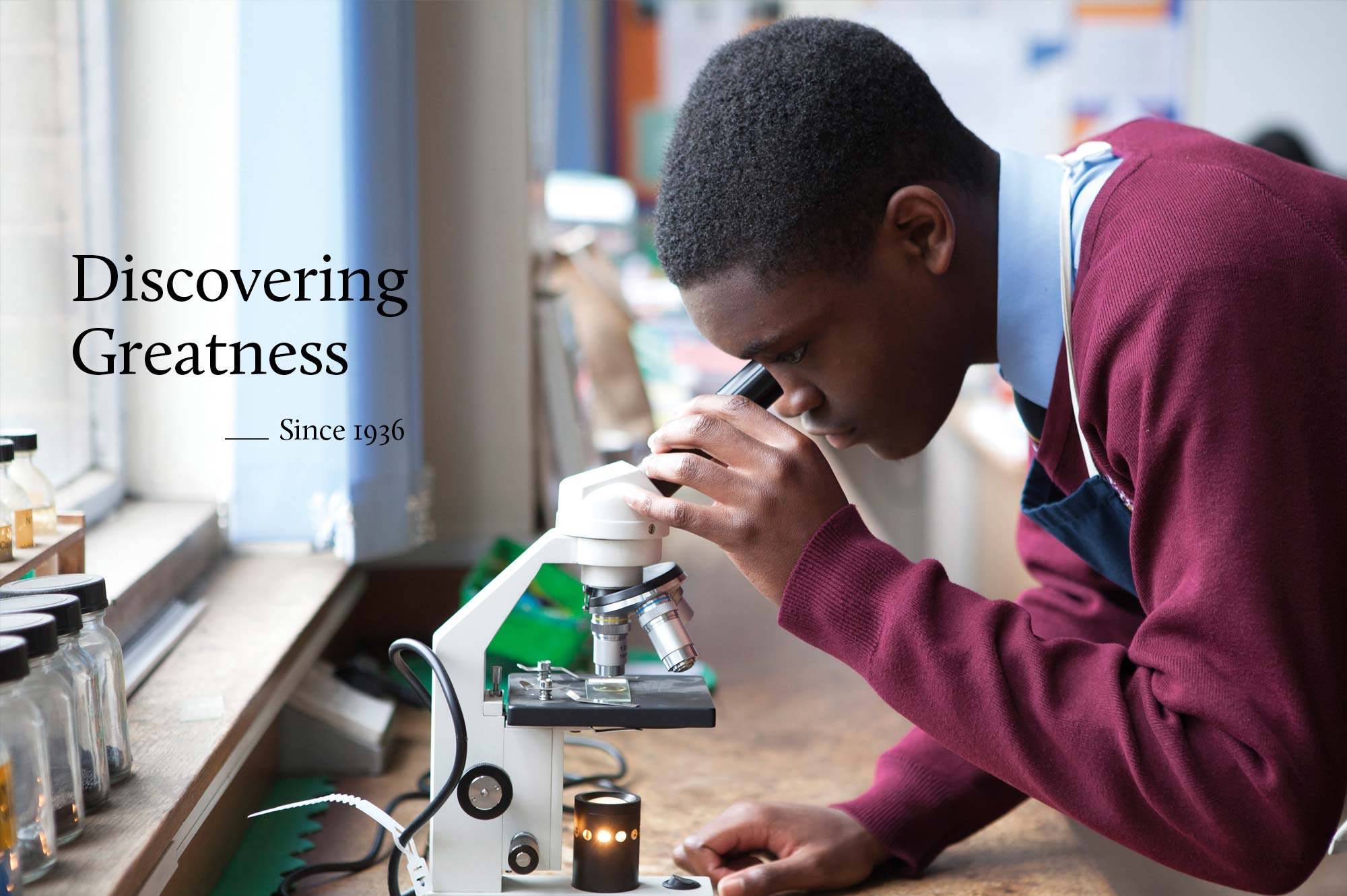 Priory School pupil looking through a microscope